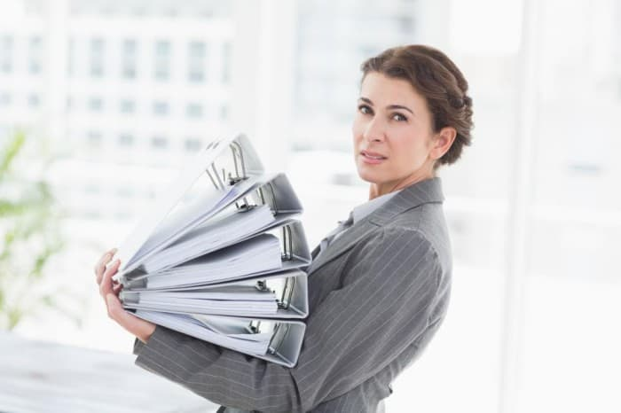 a businesswoman holding a stack of files