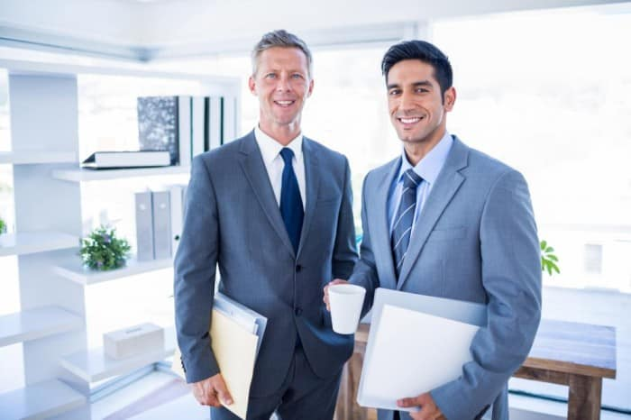 two businessmen holding files