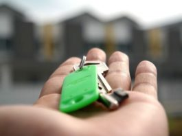 A man holding the keys to his first apartment
