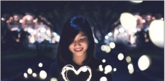 Girl Happily Holding Heart Shaped Fairy Light Strings
