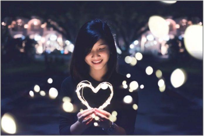 Girl Happily Holding Heart Shaped Fairy Light Strings